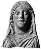 ANT-4020 - Antefix : female bust&#013 *  Antefix shaped female bust with frozen bareheaded features topped by a central line with two braids framing the face (earrings ?) Garment draped over the chest.
