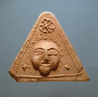 ANT-4025 - Antefix : head, wheel&#013 *  Antefix triangular shaped , with a head surrounded by two star wheel surmounted by a .