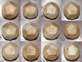 DEJ-4021 - Die : dodecahedral&#013&#013 *  Hollow dodecahedral dice with plugs to two opposite faces , all marked with figures incised Latin count (I to XII) faces.