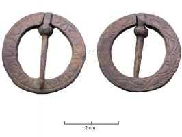 FER-7012 -  *  Fermail&#013 *  Flat ring with a constriction for a pin axis ; scrolls incised decoration on one side and an inscription on the other.