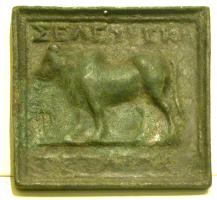 PDS-3003 -  *  Greek Weight: Seleucia Pieria&#013 *  Casting square plate with a relief on the upper face : beef walking aguche ( relating to ground) flanked by two inscriptions : above , <SELEYKION> ; below , <TETA...> .